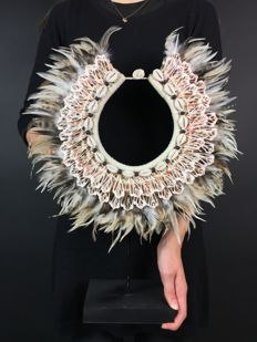 Shell necklace on a stand with rose cut shells, kauri shells and beige feathers • Indonesia