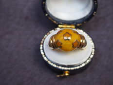 Ring in 18 kt yellow gold, set with a large amber stone topped by little gold stars.