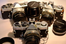 Lot of OM analogue cameras with accessories and documentation