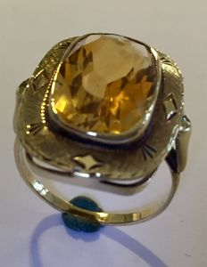 Gold ring with a citrine stone in a smooth setting, engraved edge.