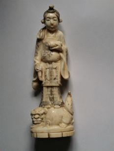 A well carved ivory statue of a religious figure on shishi lion - Japan - Early 20th century