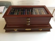 Fountain pen collection in wood cabinet