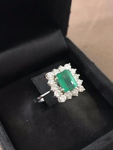Ring made of 18 kt gold with a 1 ct central emerald oblong emerald cut bordered by 14 diamonds totalling 0.70 ct. Size 15