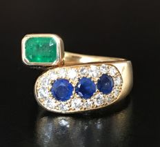 'Vous et moi' assymetrical multicoloured ring in 18 kt yellow gold decorated with an emerald, sapphires and diamonds (Total 1.42 ct)