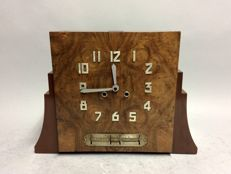 Art Deco piggy bank clock with striking mechanism and with day, month and date indication