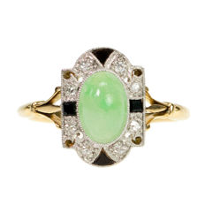 18 ct. gold ring featuring a cabochon cut Jade surrounded with Onyxes and single cut Diamonds