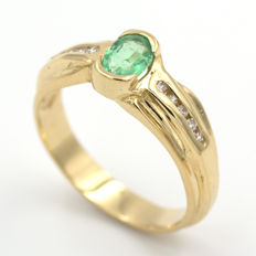 Yellow gold ring with 0.28 ct central emerald  and zirconias