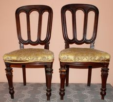 A pair of chairs upholstered in damask fabric