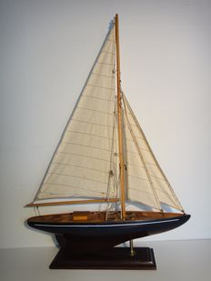 A sailboat - with a beautiful slim shape/form - well built wooden model boat.
