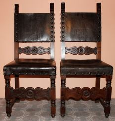 A pair of chairs upholstered in leather