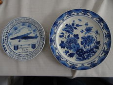 Porceleyne Fles - 2 x plates, of which one is a commemorative plate 'Pelikaan KLM December 1933' and 1 floral plate