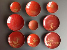 A lot with 9 wooden, lacquer Sakazuki bowls with mostly floral and plant patterns, painted in gold paint - Japan - First half 20th century.