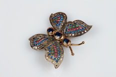 Yellow gold brooch in the shape of a butterfly with sapphires, diamonds, emeralds, red stones and blue stones.