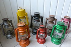 Eight original, various coloured oil lamps