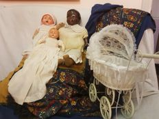Three antique dolls from 1920/1930, one of them is black and very rare, plus a lace pushchair, not antique but very nice