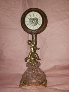 Mercedes tabletop clock - round case hold by a cherub, pedestal in faceted crystal and frame in gilt brass - circa 1940