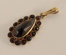 14  kt gold pendant inlaid with garnet. Size: 17 x 45 mm