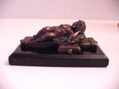 An antique paperweight, bronze sculpture of a child on a cross-shaped bed - late 19th century