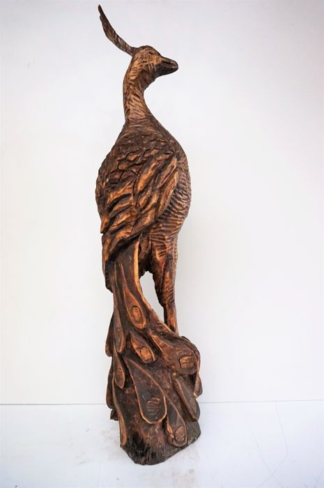 Large wooden sculpture of a peacock