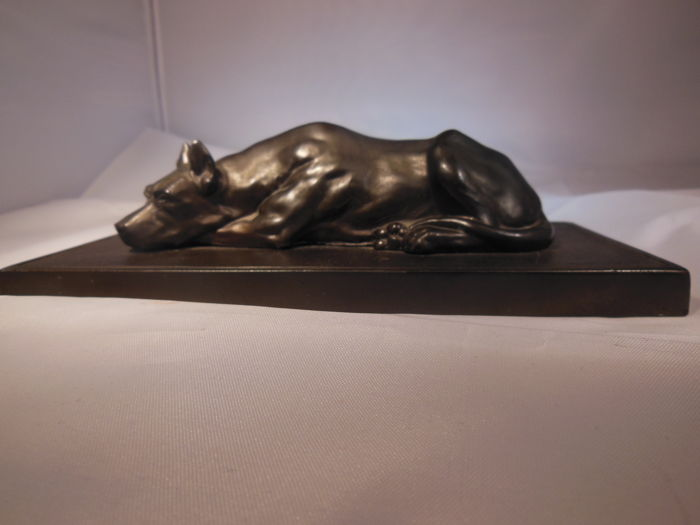 Attractive depiction of a dog lying down - metal casting - ca. 1930