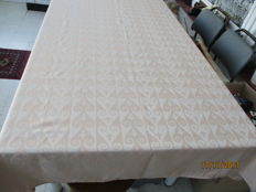 Peach coloured silk damask tablecloth.