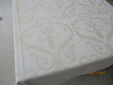 Tablecloth of shiny damask with woven pattern.
