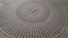 Round hand-woven tablecloth.
