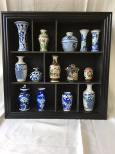Black ornamental cabinet with a collection of 14 ceramics - China/Japan - 18-20th centuries