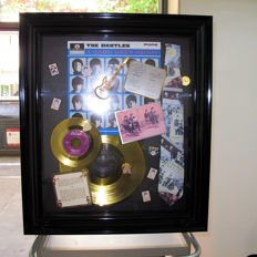 framed Beatles Memorabilia  containing a LP 33 gold rinks and a genuine 45 new original gold and 45 gold plus a lot of authentic Beatles' authentic objects.