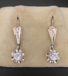Pair of Art Deco sleeper earrings in two-tone 18 kt gold, decorated with white sapphires measuring 4 mm in diameter (total 0.6 ct)