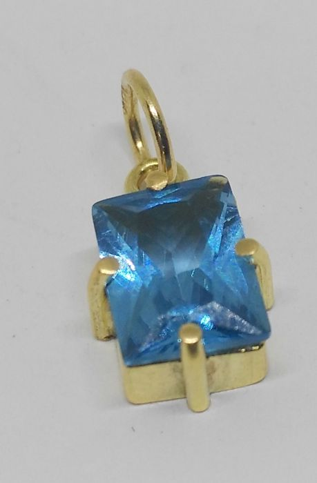 Pendant in 18 kt yellow gold with blue topaz.