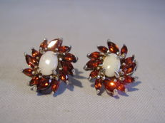 Earrings with fiery full opals (1.60 ct) and an entourage of garnet navettes (2.4 ct)