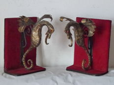 Two bookends with two wrought iron Dragons on a wrought iron bracket on wooden shelves lined in Bordeaux red velvet and black leatherette