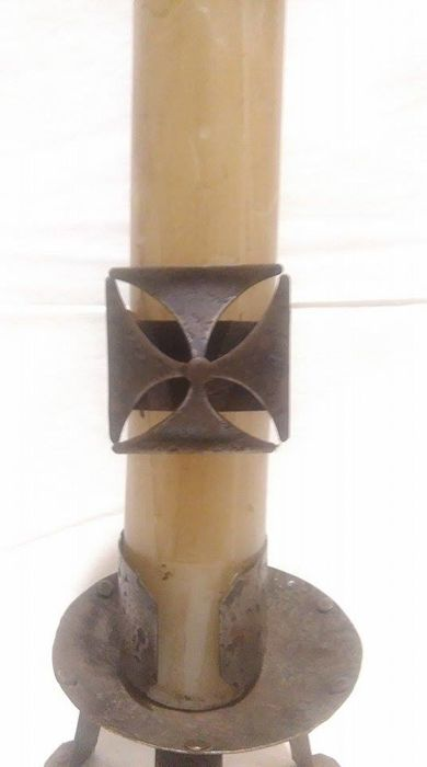 Candle on candle holder made of wrought iron with a cross pattee symbol