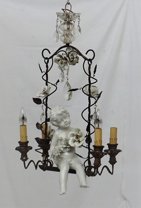 Hanging lamp in the shape of a swing with a boy and flowers between candles