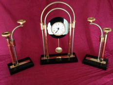 Clock and two candlesticks in brass