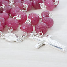 ROSARY of faceted ruby beads and sterling silver.
