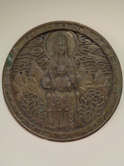 Antique bronze relief of the Virgin of Montserrat with the mountains in the background Spain, Catalonia, Montserrat Early 20th century