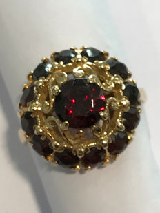 18 kt yellow gold ring with pyrope garnets. The centre garnet weighs an estimated 0.70 ct, and the 12 accent garnets have a total estimated weight of 1.20 ct. Round cut. Total weight: 5.90 grams, Italian size 13 and 1/2. Resizing option available.