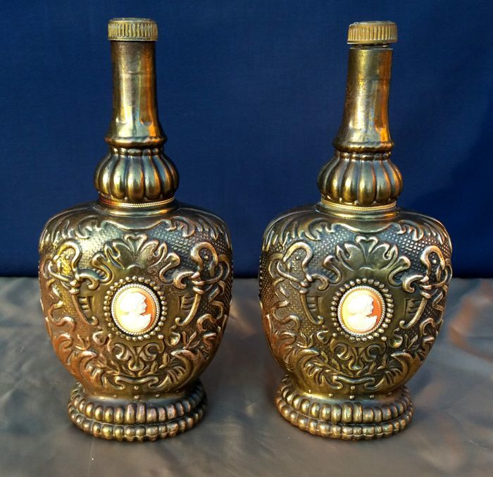Two glass scotch bottles covered in embossed brass with a cameo in the centre - Italy - 20th century