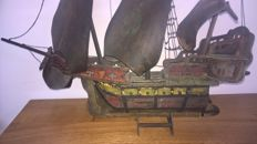 A wooden painted model boat to a caravel.