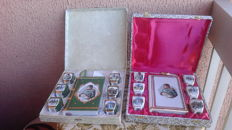 Two box sets consisting of a trio of six porcelain bowls and a book shaped bottle with a representation of Napoleon