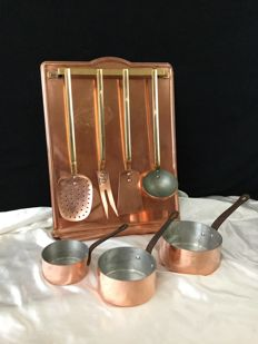 Copper kitchen utensil support with utensils and 3 copper pans