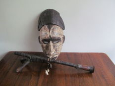 Traditionally carved wooden mask and blow pipe