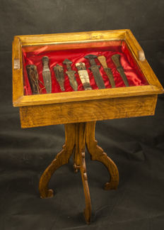 Elegant wooden cabinet with curious collection of African knives