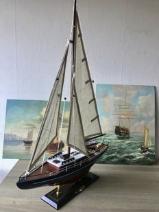 Handmade wooden sail boat model of the Concordia and two painted canvas' with sailboats.