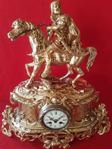 Clock in gilded bronze alloy, gold and carved with the imposing figure of a warrior and his horse, year 1890