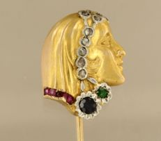 Gold with platinum pin in the shape of a woman's head set with old cut diamond, ruby, sapphire and emerald, approx. 0.26 ct in total