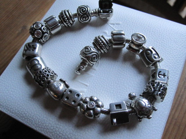 Pandora - bracelet by Pandora with 17 Pandora charms and 2 Pandora clips in sterling silver - bracelet is 21 cm long