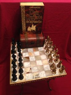 Vintage chess of Don Quijote de la Mancha on table made of turned bronze and marble, book and wooden box